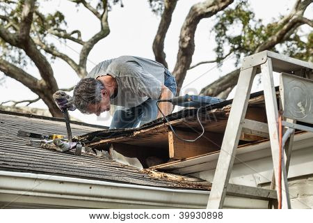 Man using crowbar to remove rotten wood from leaky roof. After removing fascia boards he has discovered that the leak has extended into the beams and decking. poster