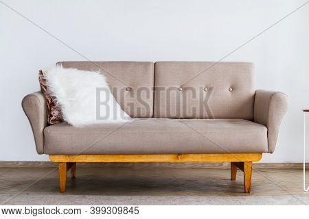 Stylish Beige Sofa With A White Fluffy Pillow