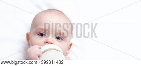 Banner With Baby Milk Bottle In Hands. Copy Space. Infant Drinking Milk. First Bottle For Baby. Arti