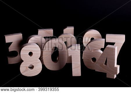 Large Random Wooden Numbers Standing Up Overlapping. Hardwood Characters On A Black Background With