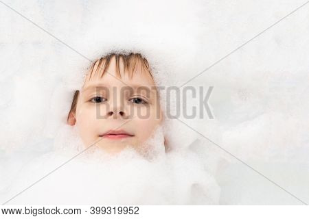 A Boy In Soapy Suds Is Washing In A Bath. Hygiene, Cleanliness Concept.