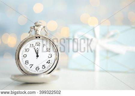 Pocket Watch On Table Against Blurred Lights, Space For Text. New Year Countdown