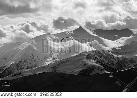 High Snowy Mountains And Cloudy Sky At Winter Evening. Silhouette Of Skydiver. Caucasus Mountains. G