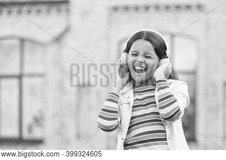 Real Joy. Child Has Music Break. Girl In Headphones. Pretty Little Girl Wear Wireless Headset. Back