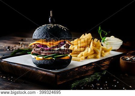 Black Burger With French Fries On Wooden Cutting Board Isolated On Black