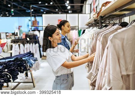 Two girlfriends choosing clothes in clothing store