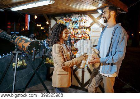Couple walking in night amusement park, fairground