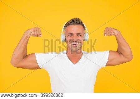 Get Powerful Sounds. Strong Man Flex Arms Yellow Background. Headphones Technology. Modern Workout A