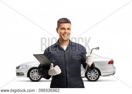 Auto mechanic worker with a silver car and a tool in his hand isolated on white background