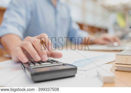 Businessman Hold Pen And Using Calculator For Calculate Budget Accountancy, Business Data. Finance A