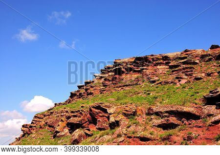 A Rock Massif Of Bright Red Color On Top Of A High Hill.
