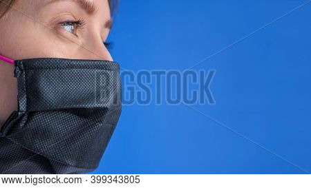 Portrait Of Woman Wearing Black Medical Face Mask, Looking Away Against Blue Background In Room At H