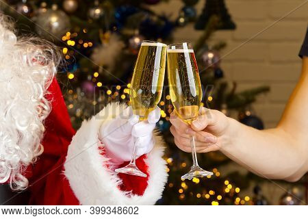 Santa Clinks Glasses Of Champagne. Clinking Champagne Glasses, Celebrating Christmas Or New Year Tog