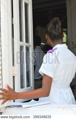 Saint Thomas, Vi. May 10, 2011. Circa: Female Caribbean Student In Her Uniform Going Inside Her Over