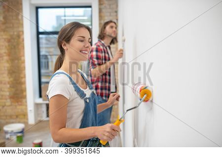 Young Couple Painting Wall In Their New House