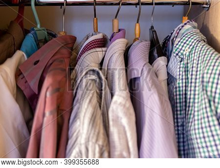 Colorful Different Clothes For Man Hanging In Wardrobe