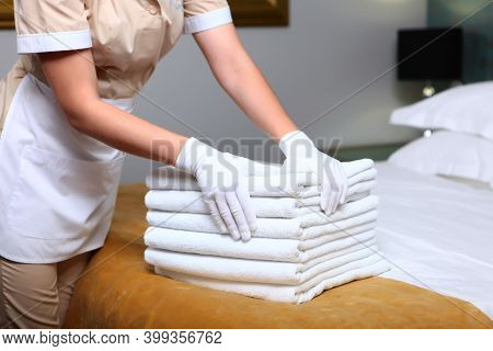 A Uniformed Maid Changes Towels In The Hotel Room. Cleaning At The Hotel. The Concept Of The Hotel B