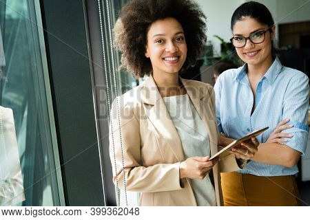 Portrait Of Successful Business Women Colleagues Using Digital Tablet In Office