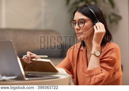 Portrait Of Adult Woman Wearing Headset And Adjusting Microphone During Online , Meeting At Home Off