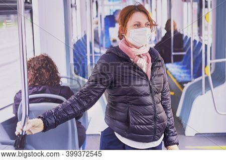 A Woman In A Medical Mask And Protective Gloves Holds On To A Handrail On Public Transport