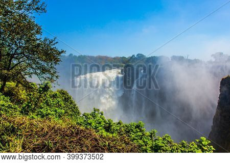 The waterfall Victoria Falls located on the Zambezi River. Giant cloud of water fog over waterfall. Journey after the wet season. Concept of extreme and photo tourism