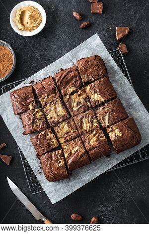 Fresh Brownies On Black Background. Delicious Homemade Chocolate Dessert, Pie Brownie With Peanut Bu