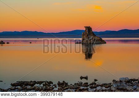 Mono Lake  in California. Magic sunset on the lake. Lime-tuff towers of bizarre shapes rise from the bottom of the lake. Magnificent reflections of tuff outliers in lake water.