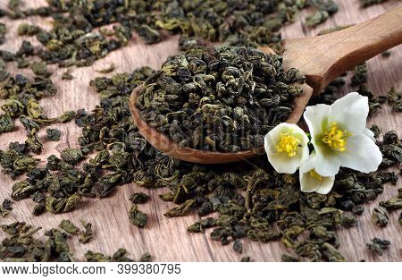 Green Tea With Jasmine. Green Tea Leaves In A Wooden Spoon And Jasmine Flowers.