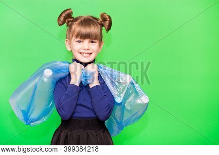 Positive Little Ecologist Girl Holding Trash Bags With Plastic Bottles Isolated On Green Background