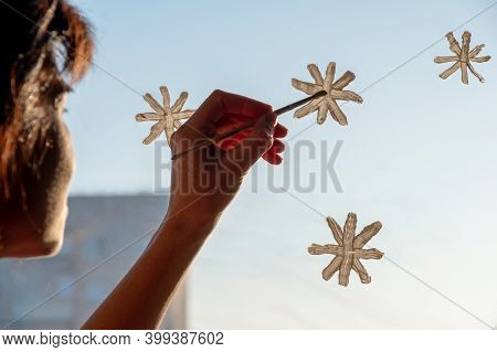 A Woman Draws Snowflakes With White Paint On The Window, Decorates The Window For Christmas, New Yea