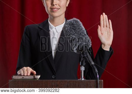 Close Up Of Young Woman Giving Oath While Standing At Podium On Stage Against Red Curtain, Copy Spac