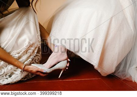 Bridesmaids Put On Leg Bride Stylish Classic Silver Shoes. Elegant Female Putting Hands On Shoes On