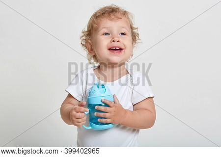 Portrait Of Little Blond Boy, Dressed In White Shirt, Posing Isolated Over Light Background With Blu