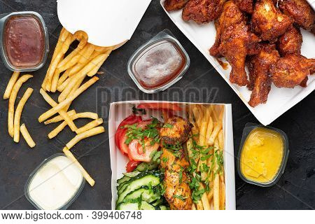 Fast Food - Box Of Crispy Grilled Chicken Legs With Greek Souvlaki And French Fries On A Dark Stone
