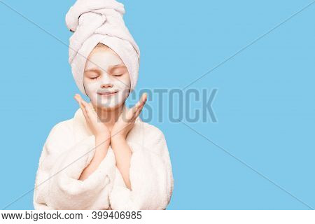 Pleased Child Girl With Wrapped Towel On Head Delighted Expression Isolated On Blue, Applies Natural