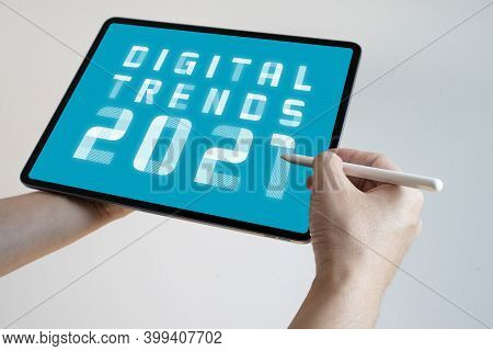 Man Hand Holding White Tablet With Digital Trends 2021 On Screen. New Trends Digital Marketing, Busi