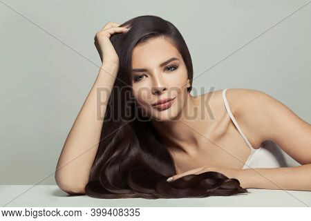 Beautiful Brunette Woman With Long Healthy Shiny Hair On White Background