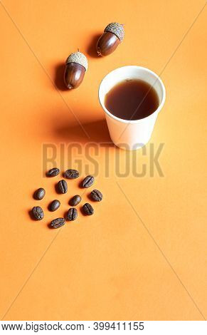 Cardboard Cup Of Eco-friendly Material With Acorn Coffee, Acorns And Coffee Beans On An Orange Backg