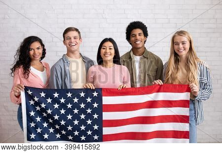 Immigration, Relocation And Study Abroad. Cheerful Young International Students Hold Usa Flag, Looki