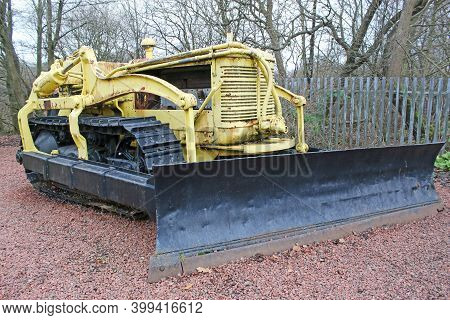 A Vintage Yellow Bulldozer In A Wood