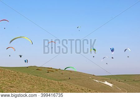 Paraglider Flying His Wing At Milk Hill White Horse, Wiltshire
