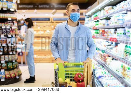 Youn Man With Shopping Cart In Supermarket Buying Groceries And Dairy Products, Walking Along The Sh