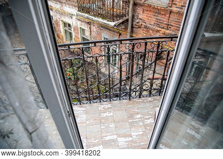 Balcony With Carved Railings. Wrought Iron Railing On The Second Floor Balcony