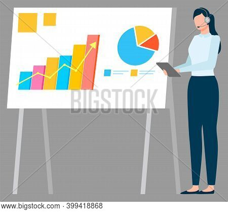 Woman Standing Near Statistics Charts And Looking On It. Lady With Tablet And Earphones Near Board W