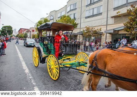 SAN FRANCISCO, USA - OCTOBER 11, 2009: Elderly woman in a red carnival costume rides an old carriage drawn by two horses.  Equestrian parade in honor of Columbus Day celebration