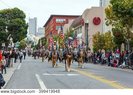 SAN FRANCISCO, USA - OCTOBER 11, 2009: Columbus Day celebration. Equestrian parade in honor of the national holiday. Dressy riders in cowboy hats carry US flags on well-groomed horses.