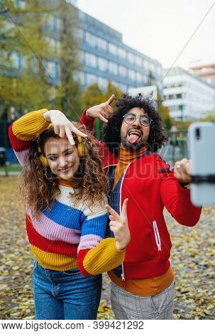 Young Couple With Smartphone Making Video Outdoors On Street, Tik Tok Concept.