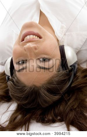 Close Up View Of Young Female Lying And Wearing Headphones