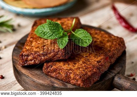 closeup of some tofu fillets on a round wooden tray, on a table