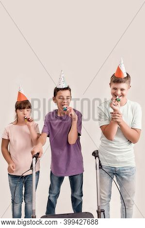 Three Disabled Children With Down Syndrome And Cerebral Palsy Wearing Birthday Caps, Blowing Whistle
